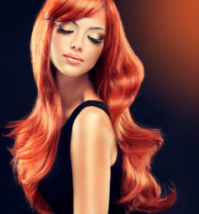 Beautiful model girl  with long red curly hair . Hairstyle and  cosmetics